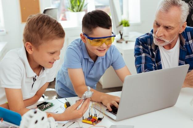 Génération moderne. gentil garçon positif assis devant l'ordinateur portable tout en tapant dessus