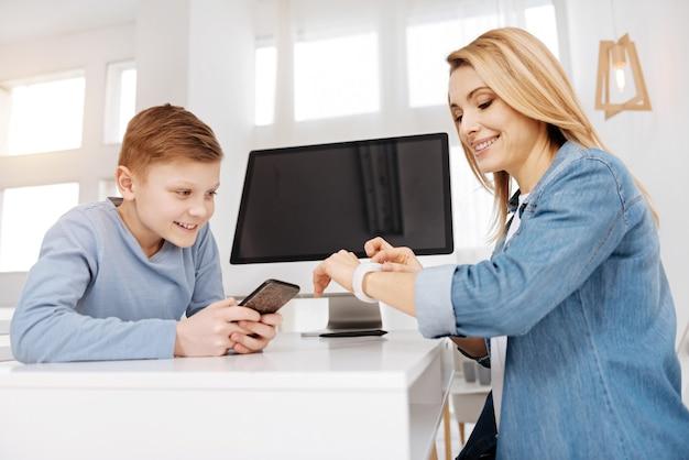 Génération moderne. heureuse belle jeune femme souriante et tenant son smartphone tout en regardant sa mère smartwatch