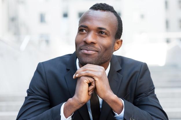 Générer de nouvelles bonnes idées. gai jeune homme africain en tenue de soirée en gardant les mains jointes et en détournant les yeux alors qu'il était assis à l'escalier extérieur
