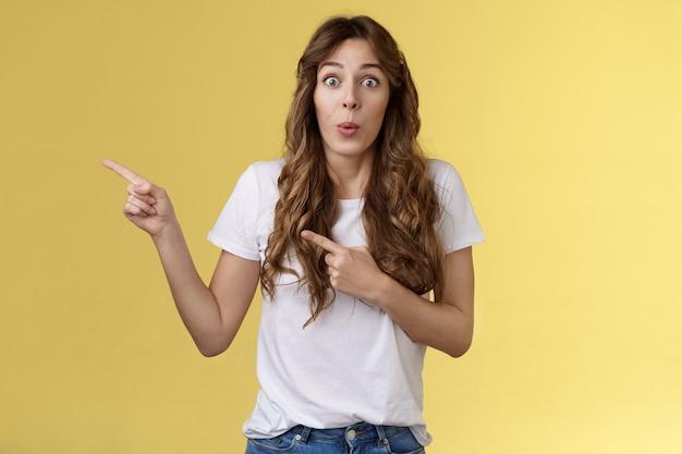 Génial, regardons de plus près. impressionné surpris séduisante petite amie caucasienne aux cheveux bouclés plier les lèvres admiration tentant essayer un nouveau produit pointant l'index gauche regarder la caméra étonné excité.