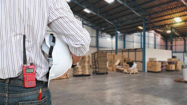 Génie industriel homme debout et mettre un talkie-walkie dans un paquet de jeans avec un casque. travailleuse vérifiant la construction avec un arrière-plan flou de grand entrepôt. l'ingénieur de concept travaille sur le site.