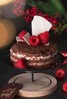Génoise trois chocolats dans une décoration de vacances du nouvel an avec des framboises. sur fond sombre