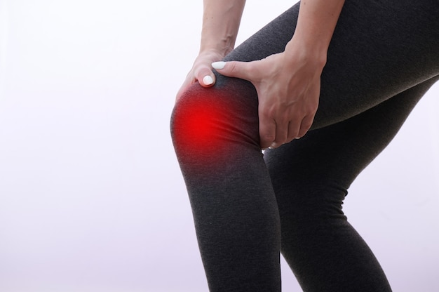 Genou blessé féminin, point sensible mis en évidence par un marqueur rouge, la femme touche sa jambe avec les mains.
