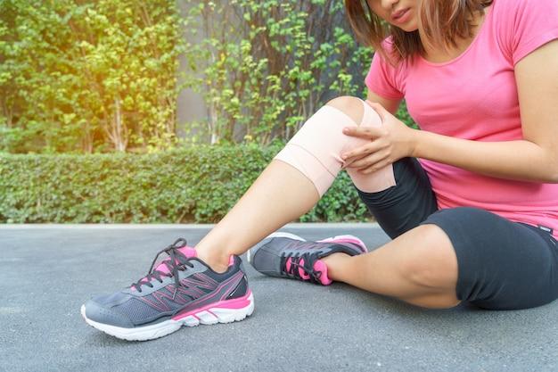 Genou de coureur de jeune femme étant appliqué bandage par lui-même dans le parc. blessure conjointe avec juste.