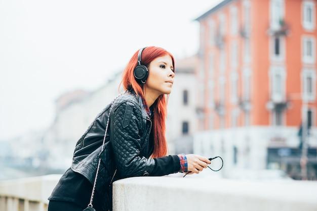 Genou figure de jeune belle rousse hispanique femme écoute de la musique avec un casque