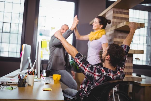 Gens d'affaires acclamant au bureau d'ordinateur