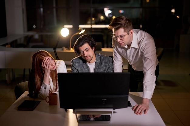 Gens d'affaires ambitieux et confiants utilisant un ordinateur de bureau, la nuit, discutant de l'explication de tâches spécifiques, de la gestion des comptes et des mouvements stratégiques. les gens tard dans la nuit dans le grand siège social