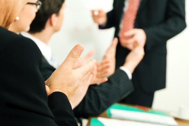 Gens d'affaires applaudir lors d'une réunion
