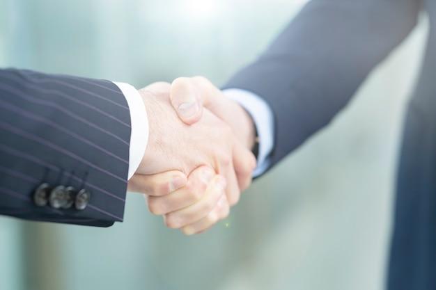 Gens d'affaires asiatiques et caucasiens se serrant la main en costumes