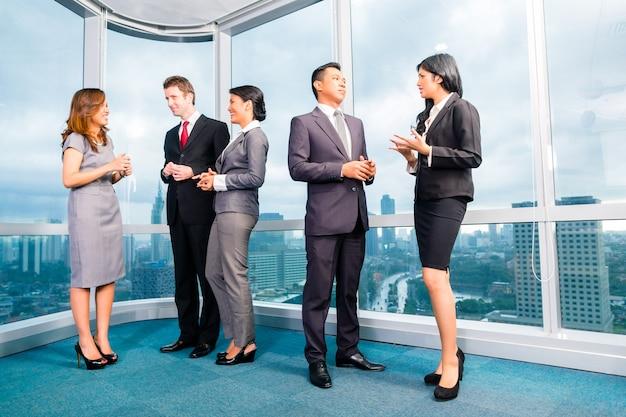 Gens d'affaires asiatiques debout et parler devant la fenêtre du bureau