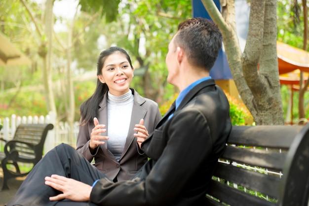 Gens d'affaires asiatiques discutant projet d'entreprise sur le banc parc