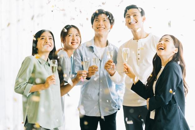 Les gens d'affaires asiatiques portent un toast à leurs verres pour célébrer les résultats