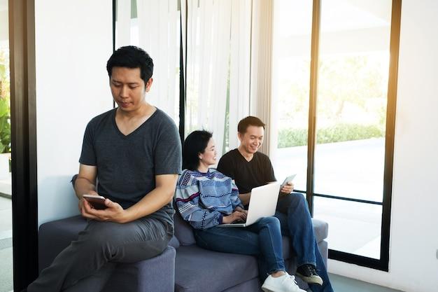 Gens d'affaires asiatiques à la réunion d'intérieur avec tablette électronique rire et téléphone intelligent.