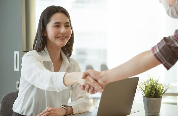 Gens d'affaires asiatiques se serrant la main, finissant la réunion