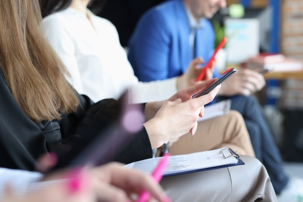 Les gens d'affaires assis à la conférence et tenant des documents et des téléphones mobiles en gros plan mains