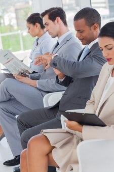Les gens d'affaires assis en ligne