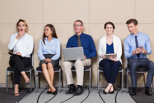 Les gens d'affaires assis en rang dans la salle d'attente