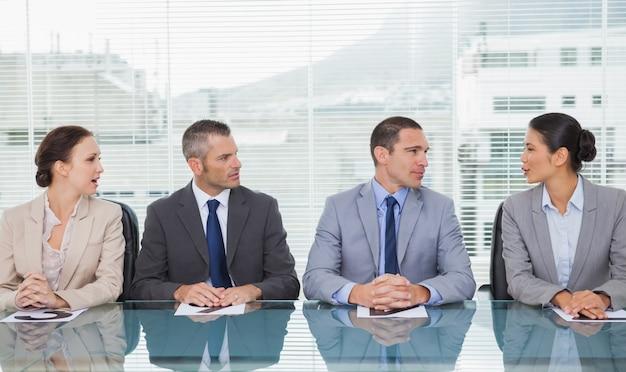 Gens d'affaires assis tout droit de parler ensemble