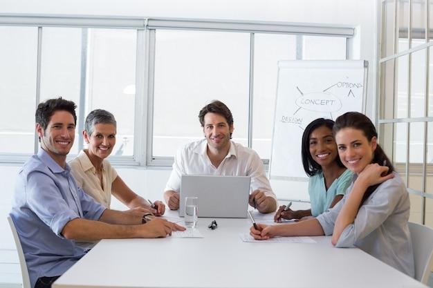 Des gens d'affaires attrayants souriant à la caméra