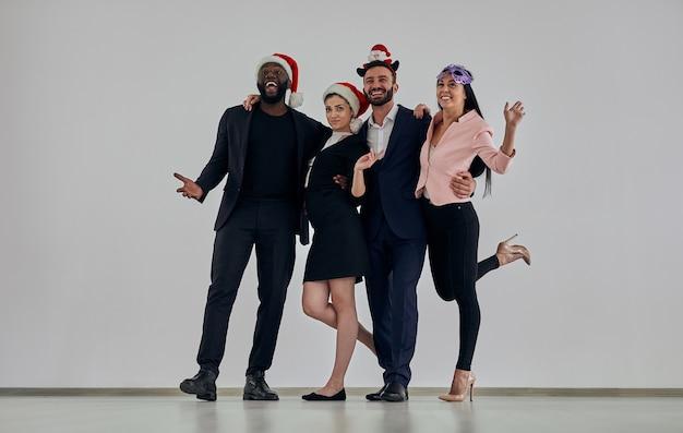Les gens d'affaires au chapeau rouge debout sur le fond du mur blanc