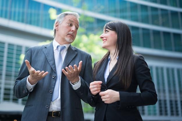 Les gens d'affaires ayant une conversation devant leur bureau