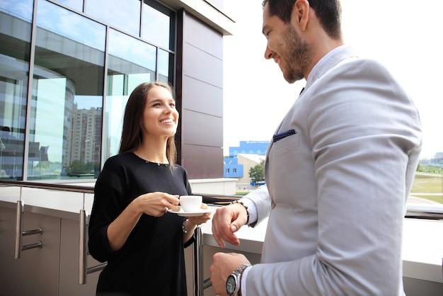 Les gens d'affaires ayant une pause sur la terrasse du bureau, boire du café en plein air.