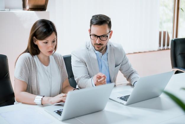 Gens d'affaires ayant une réunion autour d'une table dans un bureau moderne