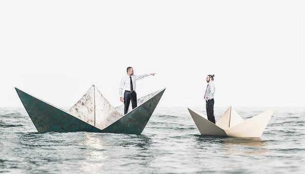 Gens d'affaires sur des bateaux en métal et en papier