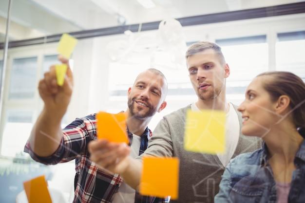 Gens d'affaires coller des notes adhésives sur la fenêtre de bureau