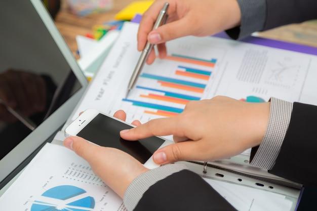 Les gens d'affaires comparant les résultats entre une carte et un mobile