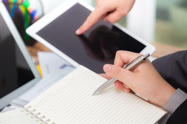 Les gens d'affaires comparant les résultats sur une tablette