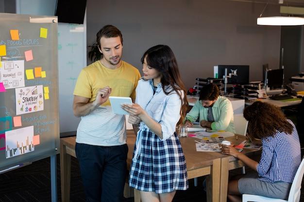 Gens d'affaires créatifs à la recherche de tablette numérique au bureau