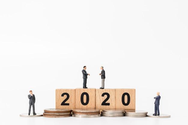Gens d'affaires debout sur un bloc de bois numéro 2020
