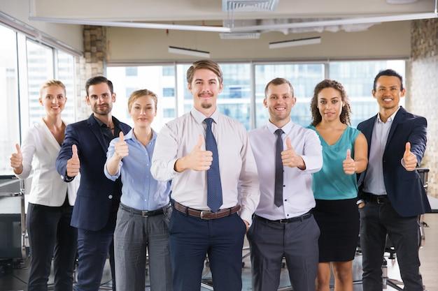 Les gens d'affaires debout dans une rangée avec les pouces jusqu'à