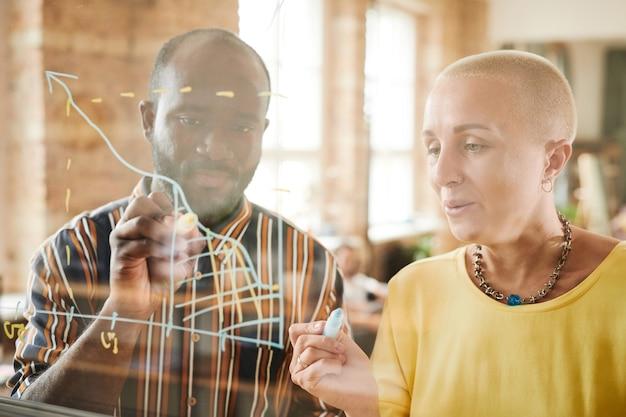 Gens d'affaires dessinant des graphiques ensemble sur un mur de verre et examinant les diplômes financiers lors de la présentation au bureau