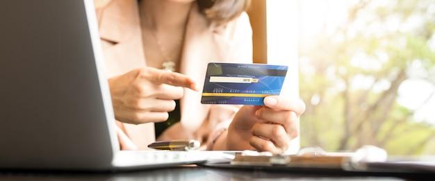 Gens d'affaires détenant des cartes de crédit et utilisant des ordinateurs portables faisant leurs achats en ligne.