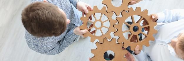 Gens d'affaires détenant des engrenages en bois en vue de dessus de bureau travaillant avec le concept de partenaires