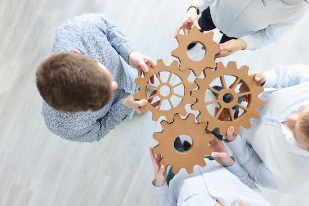 Gens d'affaires détenant des engrenages en bois en vue de dessus de bureau. travailler avec le concept de partenaires