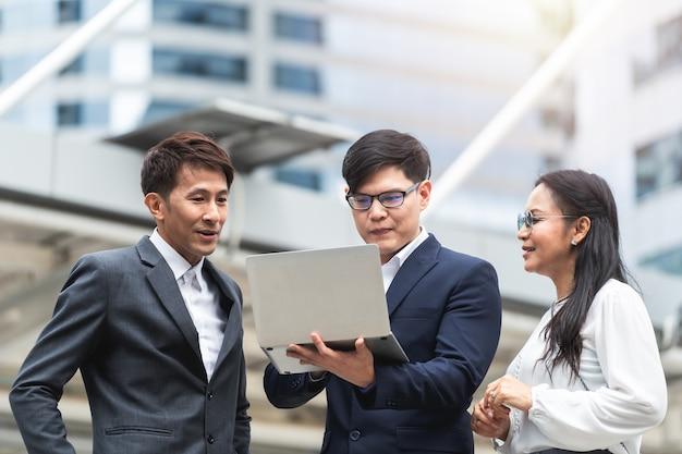 Gens d'affaires avec discussion sur ordinateur portable et travaillant ensemble à l'extérieur
