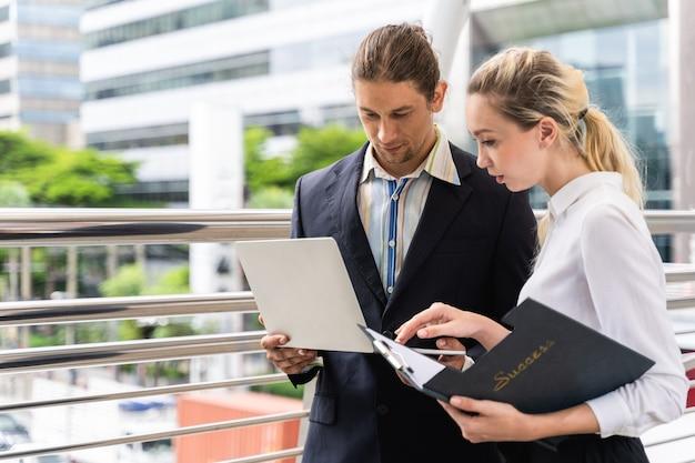 Gens d'affaires avec discussion sur ordinateur portable et travailler ensemble à l'extérieur