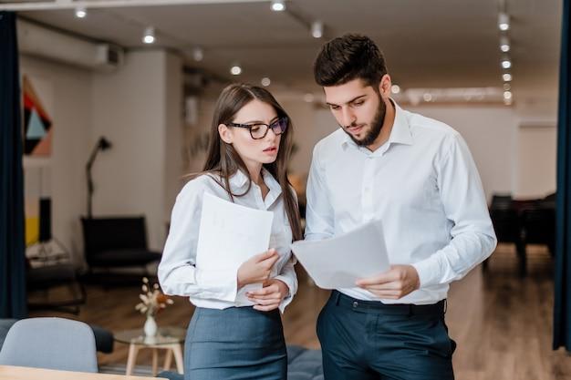 Gens d'affaires discutant d'un accord sur le papier dans le bureau moderne de l'entreprise