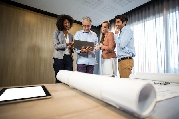 Gens d'affaires discutant sur ordinateur portable au bureau