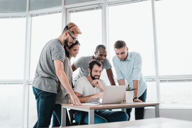 Gens d'affaires discutant sur ordinateur portable à table au bureau