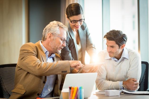 Gens d'affaires discutant sur tablette numérique