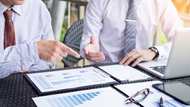 Les gens d'affaires discutent ensemble pour y travailler par document graphique et mise en place en extérieur pour la planification de la stratégie financière.