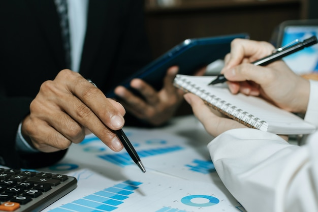 Les gens d'affaires du groupe se réunissent et planifient des activités de financement stratégique avec un rapport documentaire sur un bureau dans une salle de réunion, un partenaire, un leadership, un brainstorming, une réunion d'entreprise, un concept financier