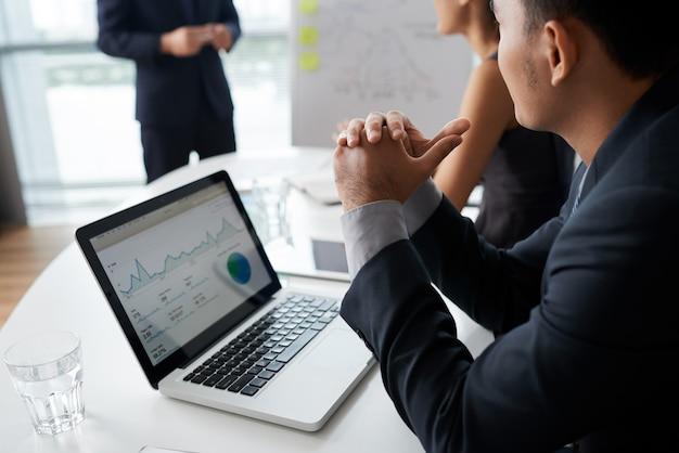 Gens d'affaires à l'écoute de leur collègue lors d'une réunion