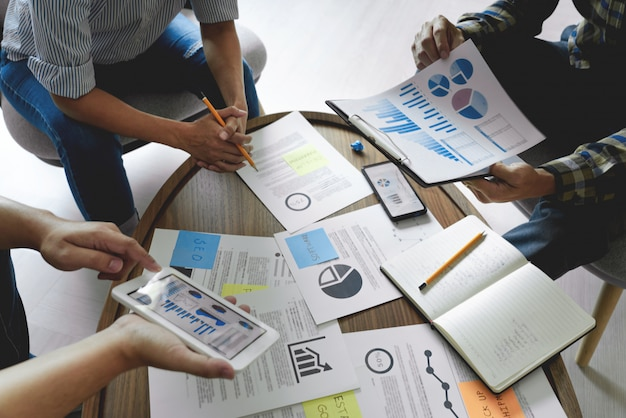 Les gens d'affaires écrivant sur des notes autocollantes pour les collègues qui pensent à un plan d'affaires stratégique ou à un problème dans le bureau de coworking, le concept de réunion d'affaires diversifiée.