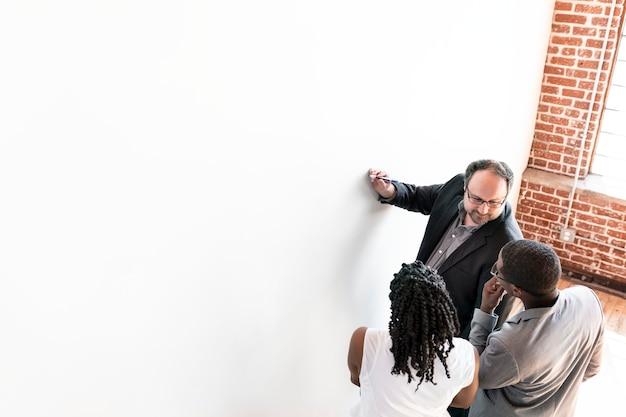 Gens d'affaires écrivant sur un tableau blanc