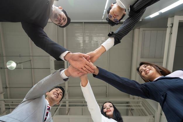 Les gens d'affaires empilent leurs mains ensemble en cercle, montrent ensemble, unissent le concept, l'équipe réussie